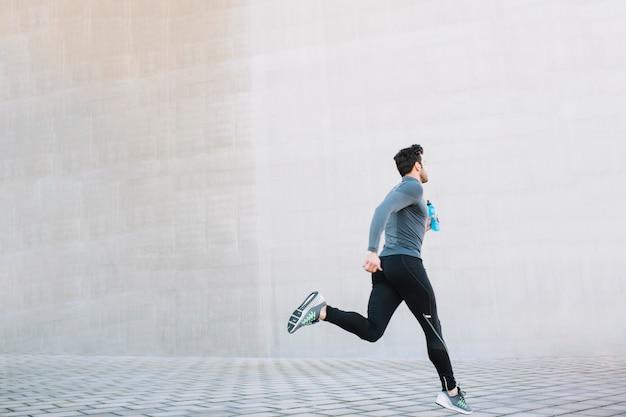 Sportive athlete running on street