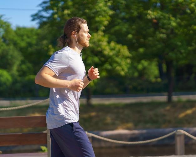 Спортивный атлетический мужчина в активной одежде работает в парке в летний день