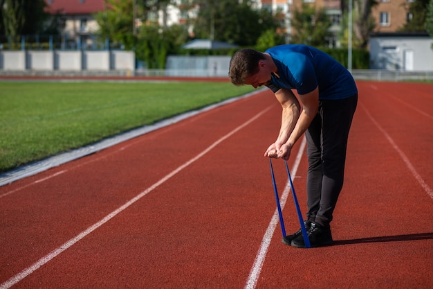 Sportive bearded man doing workout with elastic resistance band at the stadium in sunny day. empty space