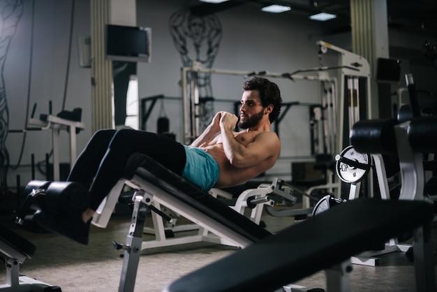 Спортивный бородатый молодой человек с мускулистым жилистым голым торсом делает упражнения для пресса на полу