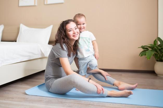 青いヨガマットで運動している赤ん坊の息子とスポーティーな美しい妊娠中の母親。アスレチックで健康的な母性。フィットネス、幸せな出産、健康的なライフスタイルのコンセプト。
