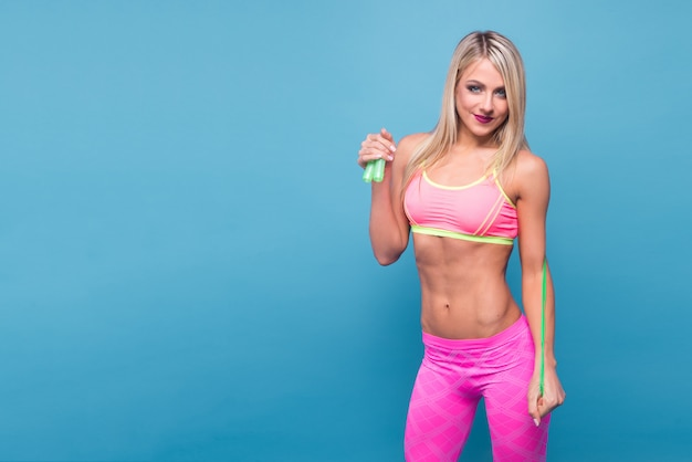 Sportive blonde girl in the pink sportswear with skipping rope on the blue