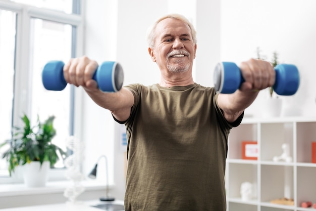 Sportive body. positive nice man lifting dumbbells while enjoying his healthy lifestyle