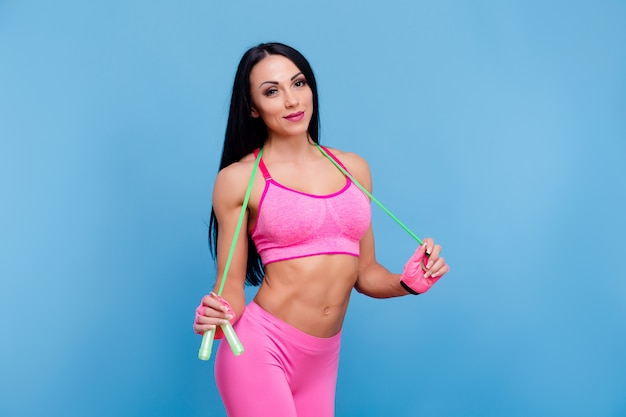Sportive brunette girl in the pink sportswear with skipping rope