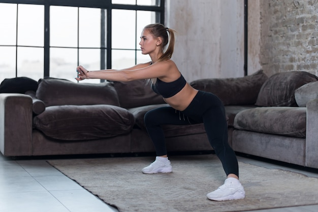Sportive caucasian female athlete in black sports bra and leggings doing side squat exercise at home