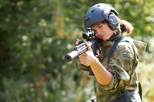 Sportive caucasian woman soldier shooting with rifle machine gun in the forest, young slim female is hunting