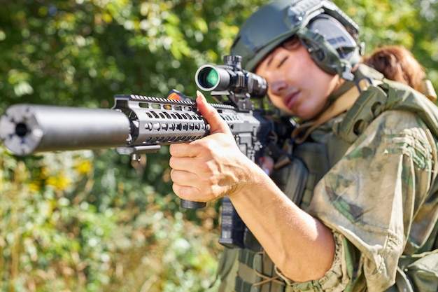 Sportive caucasian woman soldier shooting with rifle machine gun in the forest