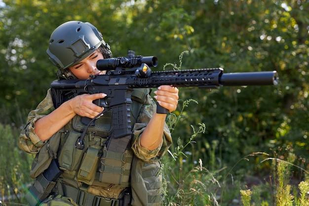 숲에서 소총 기관총으로 촬영 낚시를 좋아하는 백인 여자 군인
