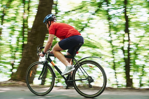 Sportive clothes. cyclist on a bike is on the asphalt road in the forest at sunny day