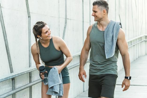 Спортивная пара гуляет по городу после фитнеса или пробежки w