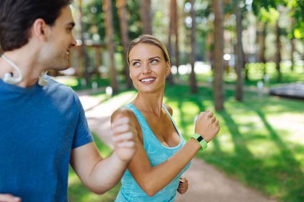 Sportive couple. delighted happy woman looking at her boyfriend while jogging together with him