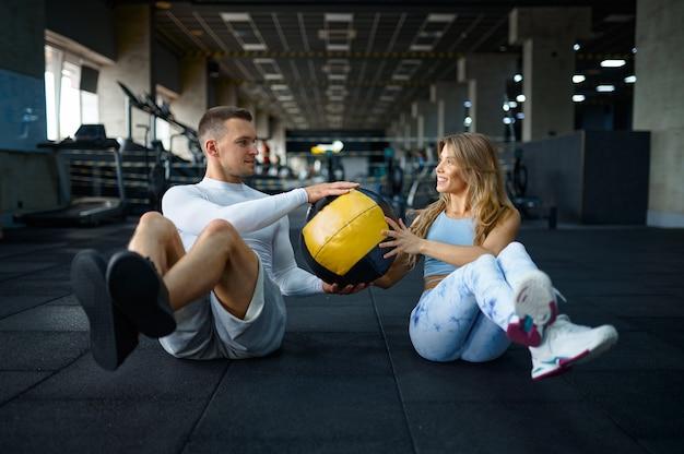 Спортивная пара занимается фитнесом с мячом, тренируясь в тренажерном зале. спортивная (ый) мужчина и женщина на тренировке в спортивном клубе, активный здоровый образ жизни, физическое благополучие