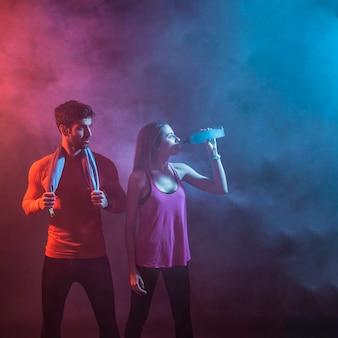 Sportive couple in dark studio