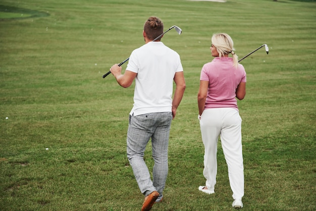 Sportive couple playing golf on a golf course, they stand to the next hole