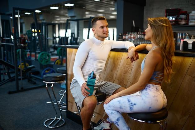운동을 좋아하는 커플은 피트니스 훈련 후 체육관 바의 카운터에서 휴식을 취합니다.