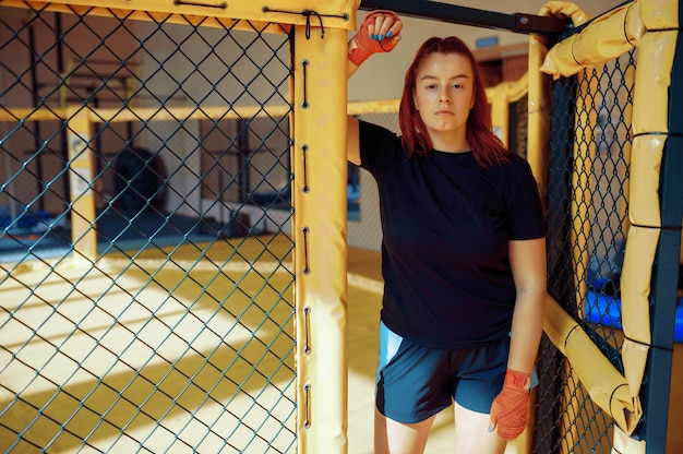 Sportive female mma fighter in bandages poses in a cage in gym.