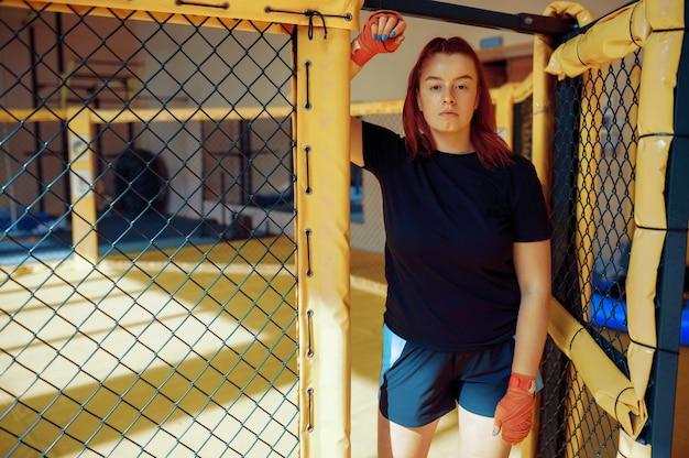 붕대에 낚시를 좋아하는 여성 mma 전투기는 체육관에서 감금소에 포즈를 취합니다.