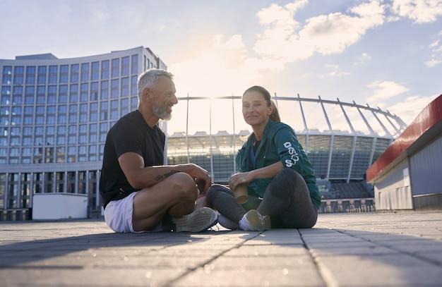 Спортивная пара разговаривает, сидя на открытом воздухе после утренней тренировки в солнечный летний день
