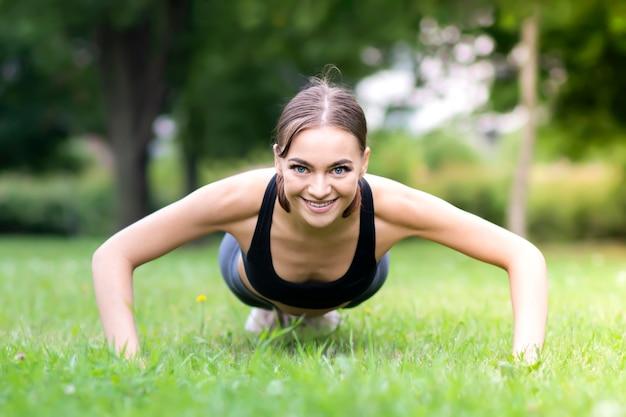 Спортивная стройная девушка в хорошей форме, молодая красивая счастливая женщина делает упражнения, отжимается