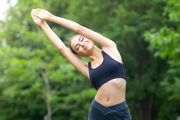 Спортивная посадка стройная девушка в хорошей форме, молодая красивая счастливая женщина делает упражнения, тренировки в