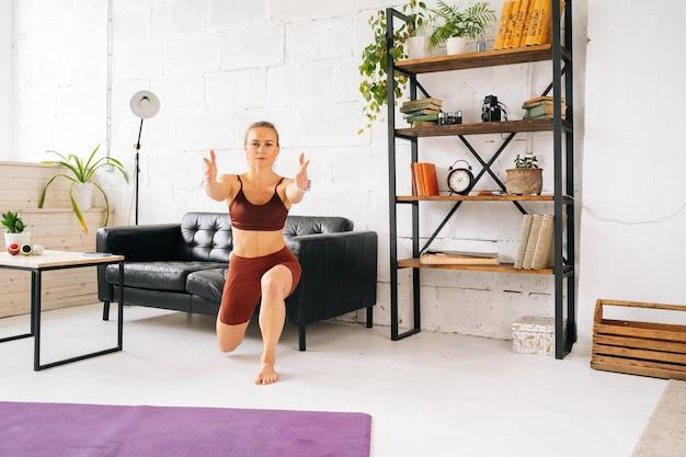 床に裸足で立って運動するスポーツウェアを身に着けている完璧な運動体を持つスポーティーフィットの若い女性。健康的なライフスタイルと家庭での身体活動の概念。