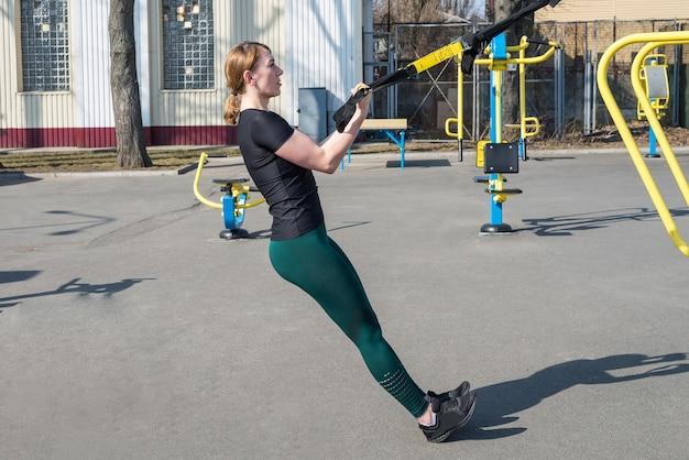 屋外でのフィットネスのためにtrxストラップで腕立て伏せをする運動をしているスポーティーなフィットネス女性。トレーニング、ボディービル、スポーツとトレーニング、ライフスタイルの概念