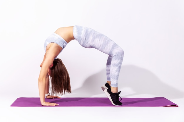 Sportive fitness woman in white top and tights practicing yoga urdhva dhanurasana pose, working out