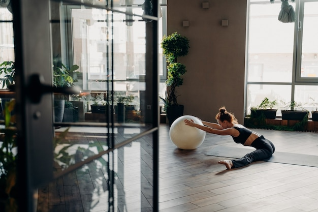 Sportive flexible woman with hair in bun stretching legs while sitting in split position on yoga mat in fitness studio, using fitball and relaxing after workout. wellness and body care concept
