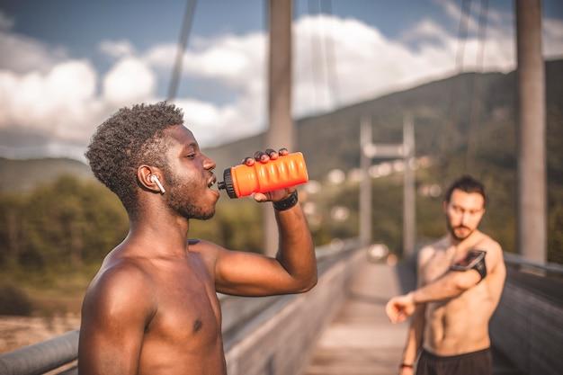 Спортивные друзья тренируются на свежем воздухе и отдыхают после пробежки