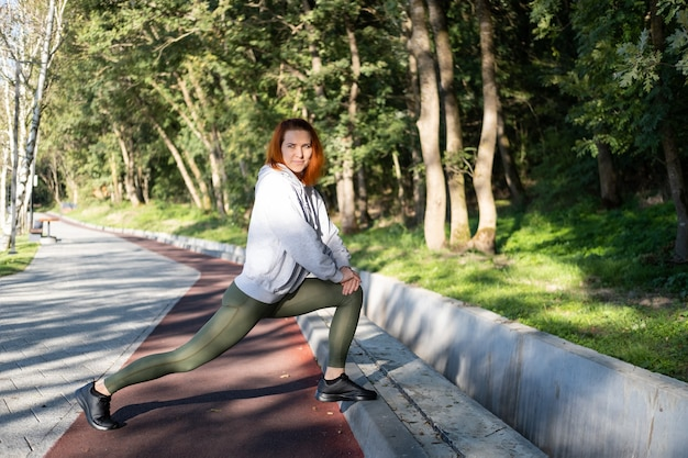 Sportive ginger woman in sport clothes working out in park sports and fitness lifestyle