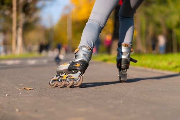 A sportive girl is rollerblading in an autumn park