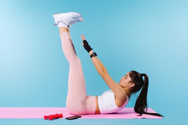 フィットネスマットの上のスポーティーな女の子は、プレスのための運動をします。空のスペースと青い背景。