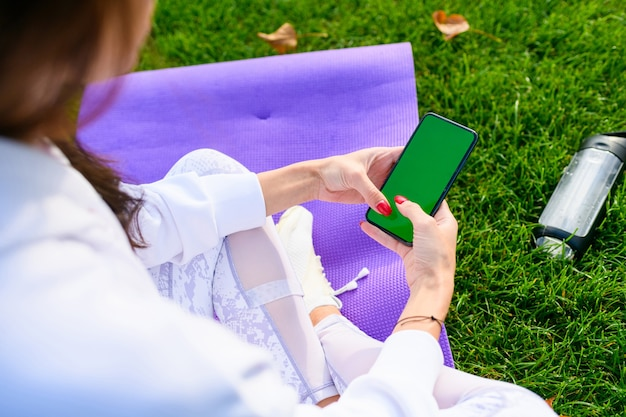 낚시를 좋아하는 소녀는 매트에 앉아, 빈 녹색 화면이 있는 전화를 들고, 운동 후 병에서 물을 마시고, 야외 피트니스
