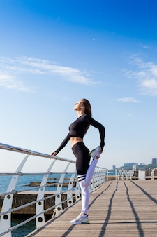 Sportive girl stretching near the sea