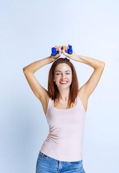 1つのダンベルでトレーニングしたり、製品を宣伝したりするスポーティーな女の子。