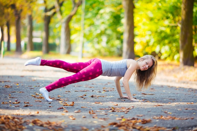 Sportive girl working out doing push ups press exercise in summer park