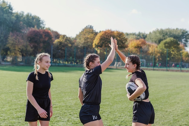Sportive girls holding soccer ball and high five