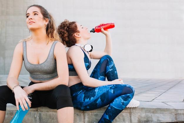 Sportive girls taking rest on street