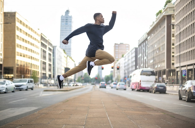 Sportive guy jumping high in the street