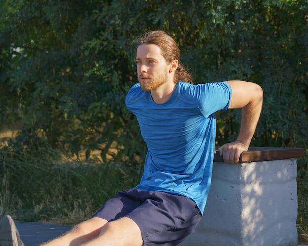 Спортивный парень тренирует трицепсы во время отжиманий на скамейке в парке в летний день