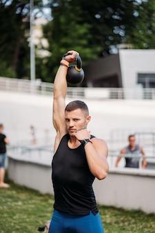 ケトルベルでトレーニングするスポーティーな男。体格の良いハンサムな男。強さとモチベーション。