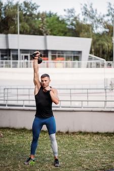 Ragazzo sportivo allenamento con kettlebell. bell'uomo con un buon fisico. forza e motivazione.