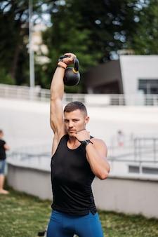 케틀벨로 훈련하는 낚시를 좋아하는 남자. 좋은 체격을 가진 잘생긴 남자의 사진입니다. 힘과 동기.