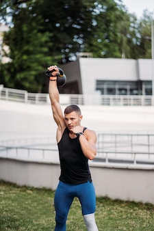 ケトルベルでトレーニングするスポーティーな男。