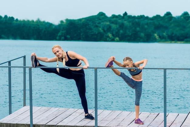 Спортивная счастливая мать тренируется с маленькой дочкой