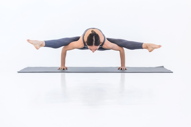 Sportive healthy woman practicing yoga doing twine handstand pose on mat on white background