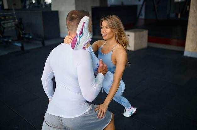 스트레칭 운동을 하는 낚시를 좋아하는 사랑의 커플, 체육관에서 피트니스 훈련