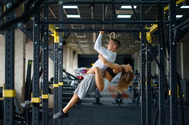 낚시를 좋아하는 사랑의 커플은 수평 막대에서 포옹하고 체육관에서 훈련합니다.