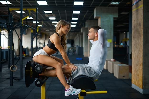 낚시를 좋아하는 사랑 커플은 크런치 머신에서 포즈를 취하고 체육관에서 훈련합니다.
