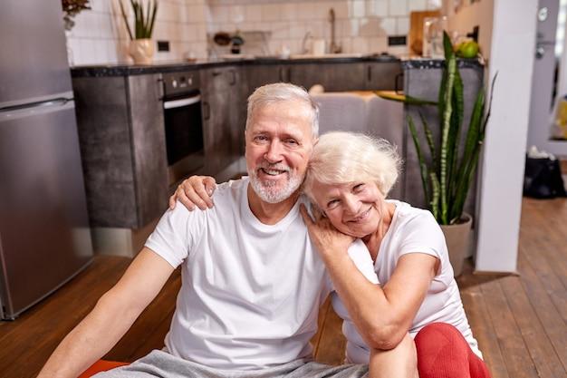 50〜60歳のスポーティーな男性と女性が床に座り、トレーニング、スポーツエクササイズ、笑顔のカメラを見て、一緒に幸せ